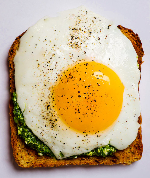 Fried egg sunny side up on whole wheat toast with spinach pesto